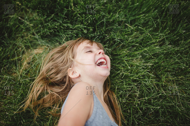Exuberant young girl laughing while lying in grass