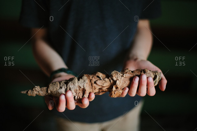 Boy holding wood material he is carving
