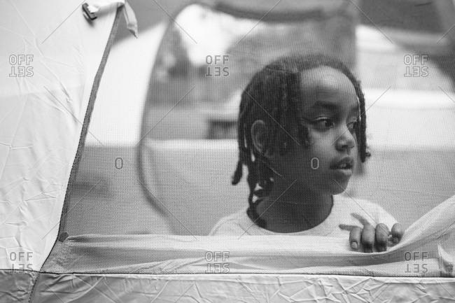 Young girl looking out from a tent window