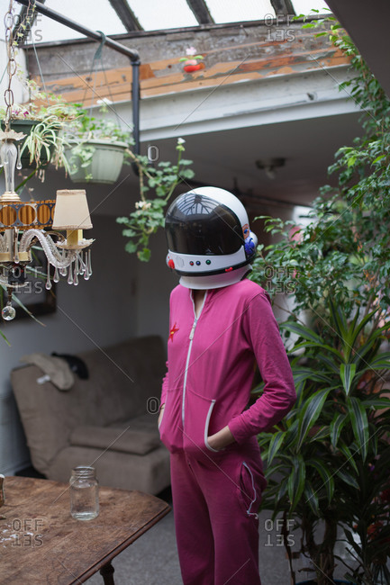 A woman stands under a skylight in a pink jumpsuit and spacesuit helmet