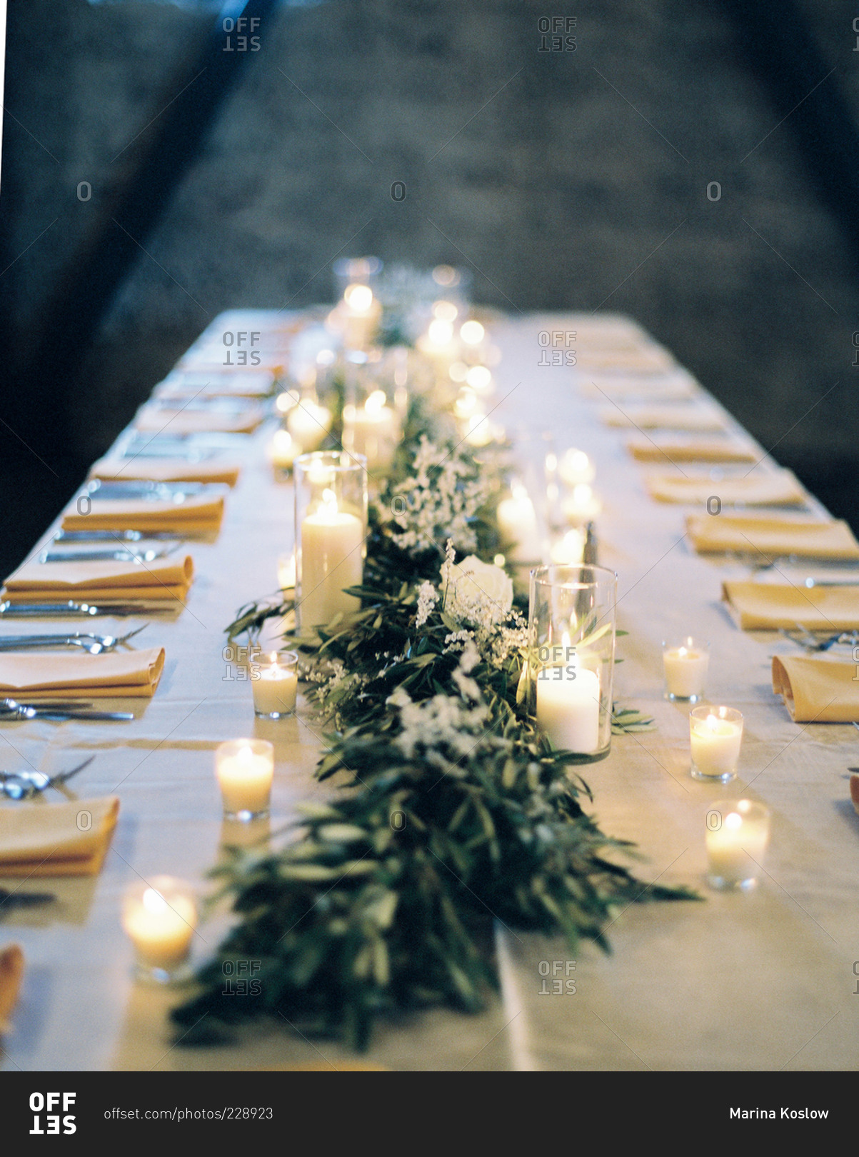 View Down A Long Candlelit Table With Olive Branches At Wedding