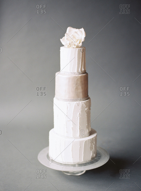 Elegant tall, narrow wedding cake on gray background