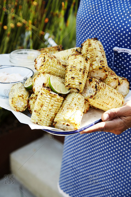 A woman carries a tray of grilled corn