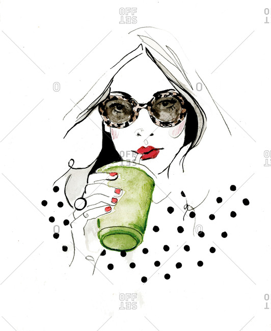 A woman in dotted shirt and sunglasses sipping green drink through straw