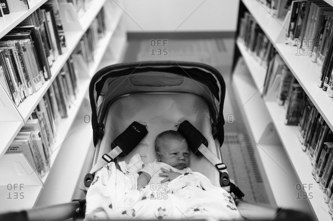 A baby in a bassinet in a library