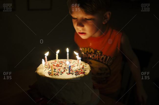 A boy blows out candles on a birthday cake with sprinkles
