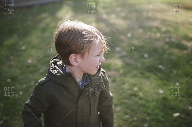 A boy wearing a parka in a yard