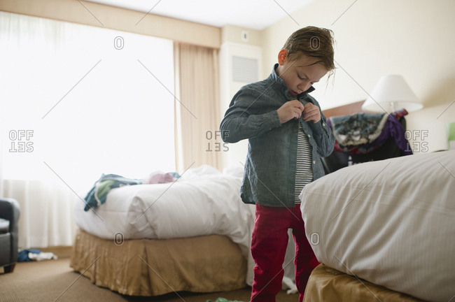 A little boy buttons his shirt in a hotel room