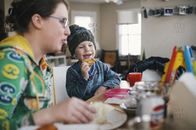 A mother and son laugh together while eating breakfast