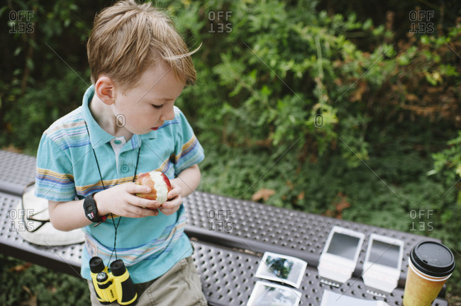 A boy with binoculars eats an apple and looks at instant photographs