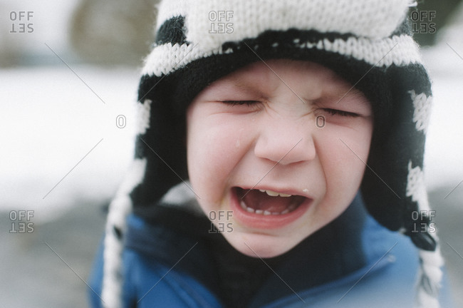 A little boy cries outside in the snow