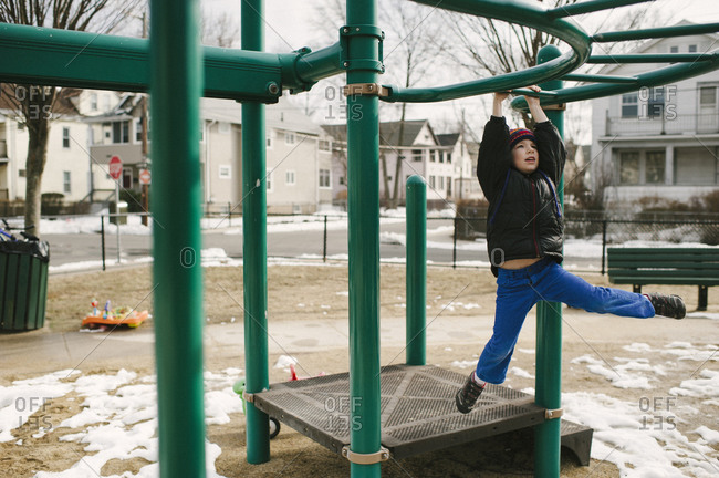 A little boy swings on monkey bars in a park