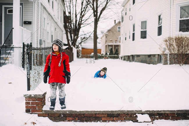 Two boys play in the snow outside of their house