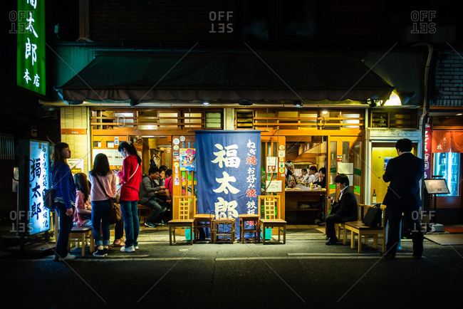 Osaka, Japan - May 19, 2015: People waiting in front of a small restaurant in Osaka, Japan