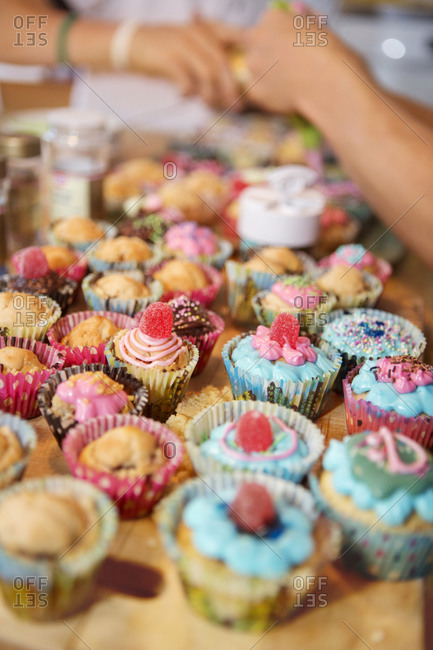 Teenage boys decorating cupcakes