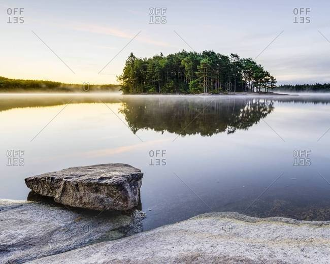 Trees on island reflecting at water