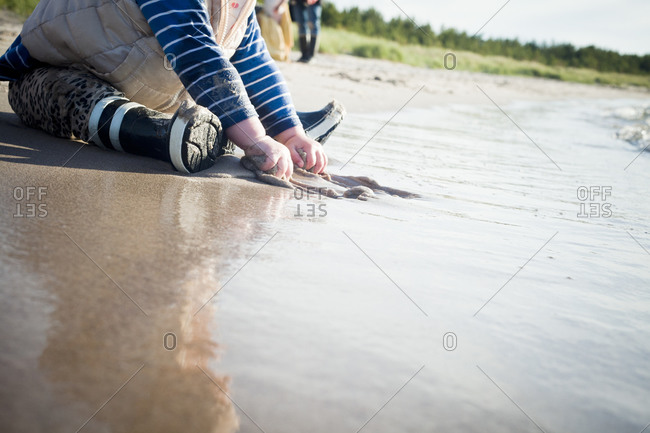 Child playing in sand on beach