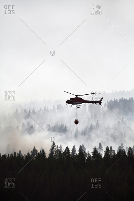 Silhouette of a helicopter dumping water on forest fire