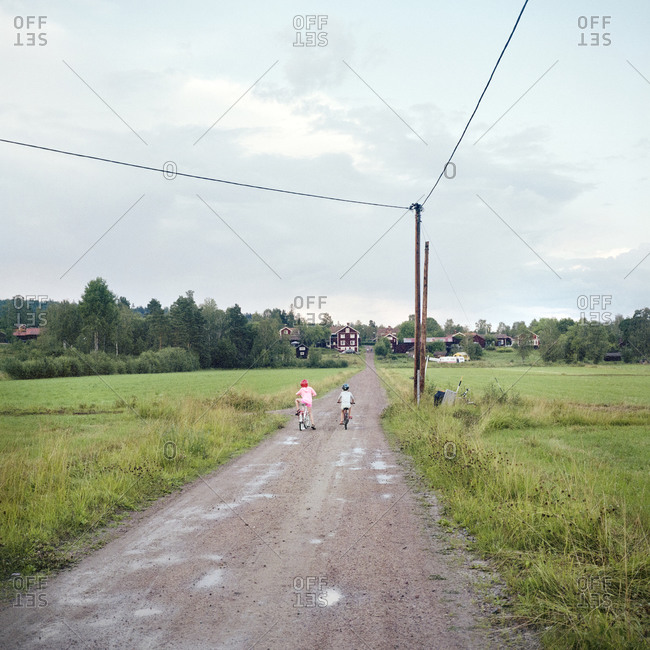 Children cycling on dirt road
