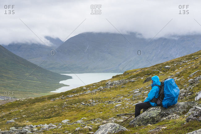 Hiker sitting on a mountain slope