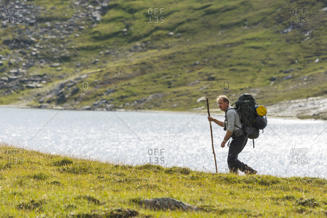Hiker in mountains with walking stick