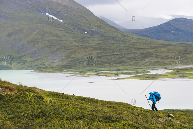 Lone hiker in mountains by mountain lake