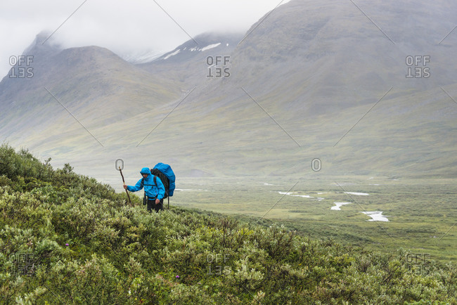 Hiker trekking up a slope mountains