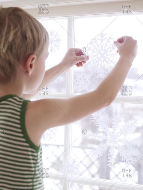 Boy sticking decorations on window