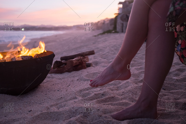 Close up of woman sitting by the fire on a beach