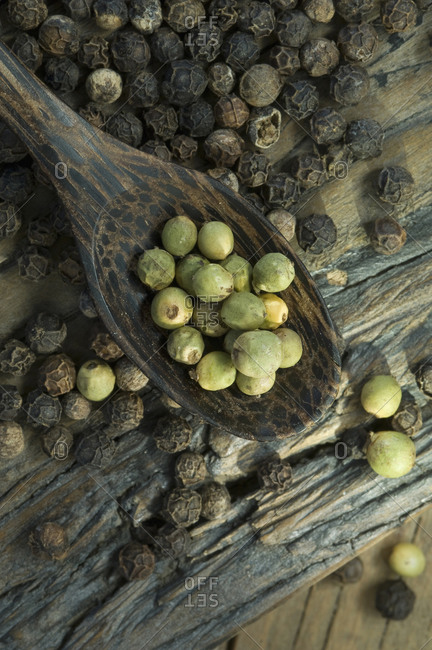 Green and black peppercorns on a wooden spoon and surface