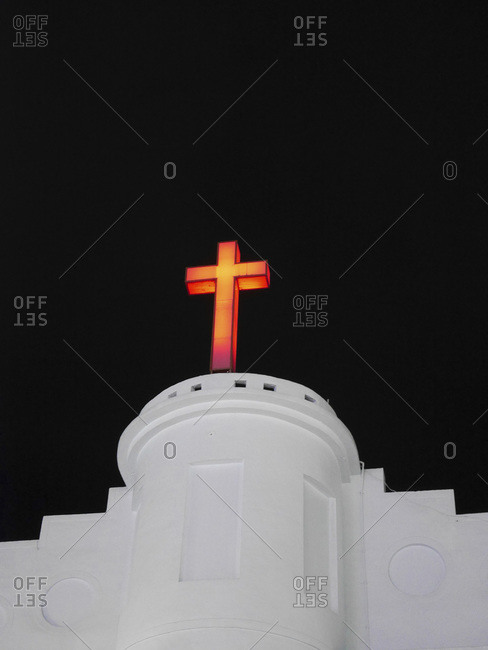 Lighted crucifix on a white church at night, Taiwan