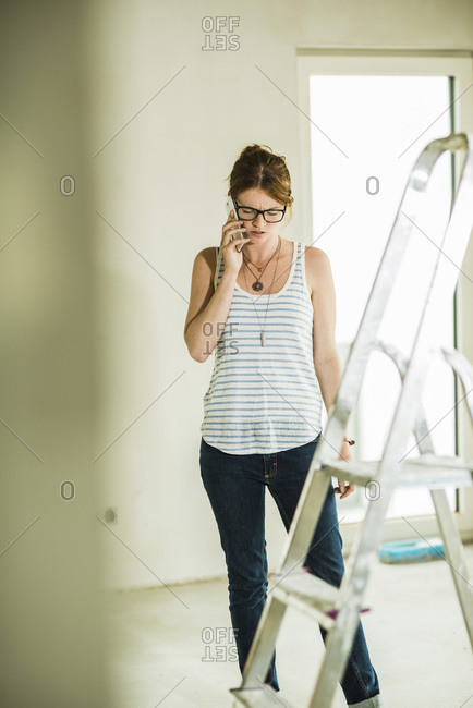 Young woman renovating talking on cell phone