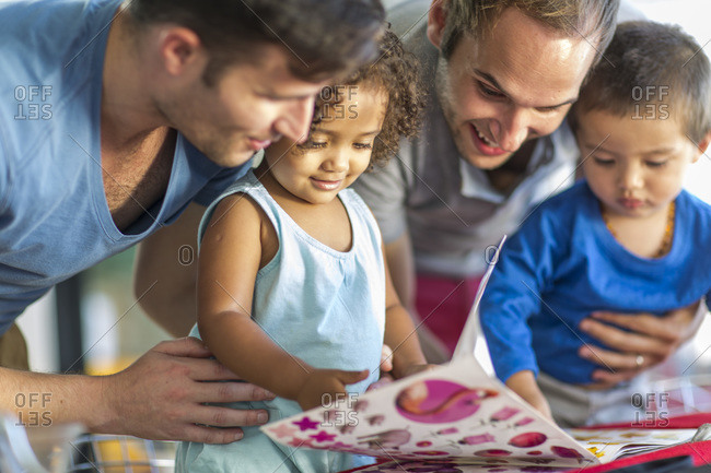 Two men with two kids looking at picture book