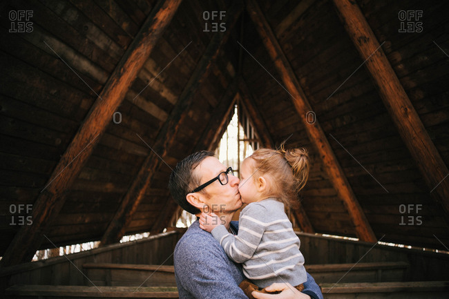 A father kisses his daughter in a wood structure