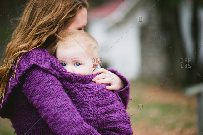 A mother wraps her baby in her sweater