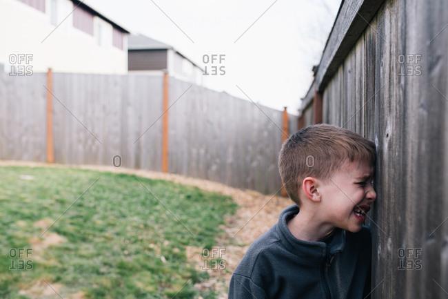 A boy peeks through a hole in a fence