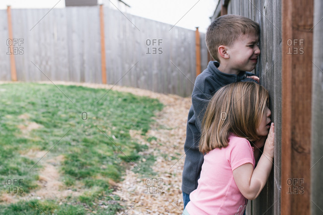 A brother and sister peek through holes in a fence