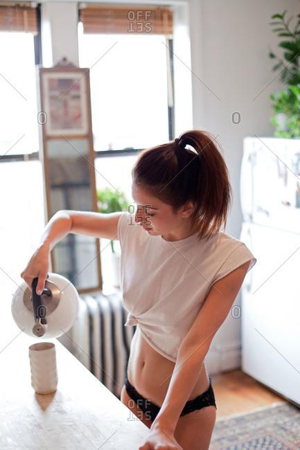Young woman pouring tea into a mug