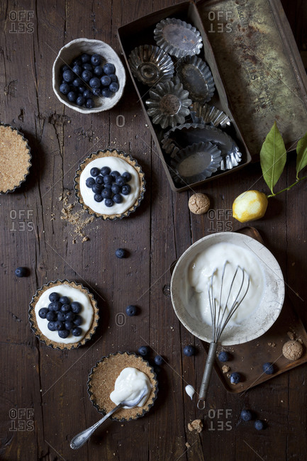 Overhead view of pastry shells being filled with yogurt and topped with blueberries
