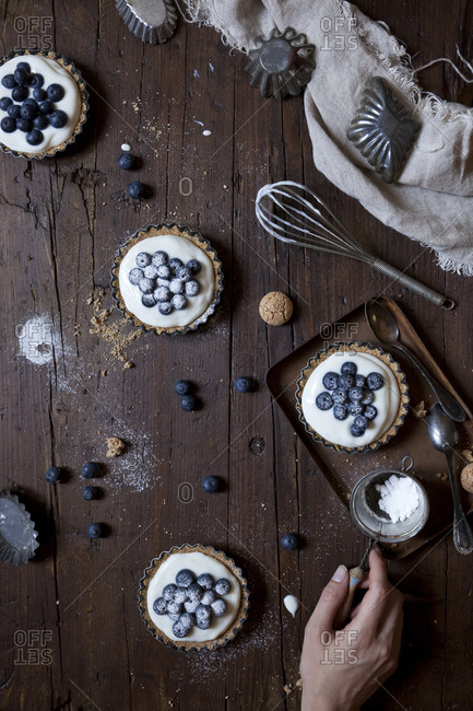 Yogurt berry tarts being dusted with confectioner's sugar