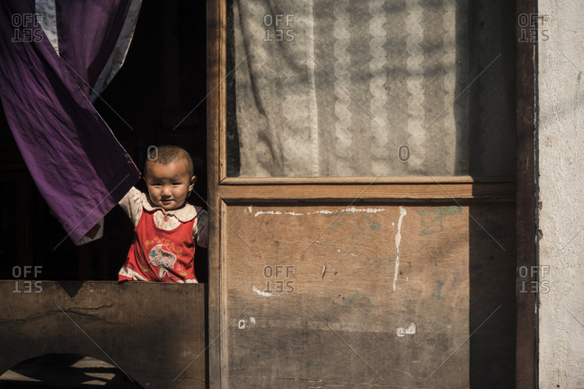 Boudhanath, Nepal - April 11, 2014: A little girl looks out of her window in Nepal