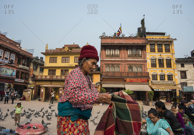 Boudhanath, Nepal - April 11, 2014: An old woman folds up a blanket in a city square in Nepal