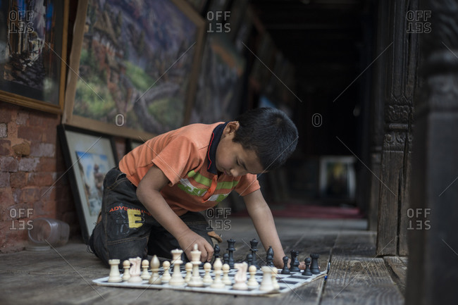 Bhaktapur, Nepal - April 12, 2014: A boy plays chess alone in a gallery