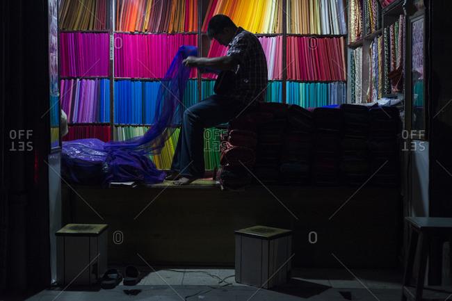 Kathmandu, Nepal - May 21, 2014: A man in a fabric store unwraps blue fabric