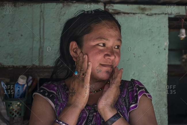 Thimi, Nepal - May 21, 2014: A woman touches her face and looks to the side