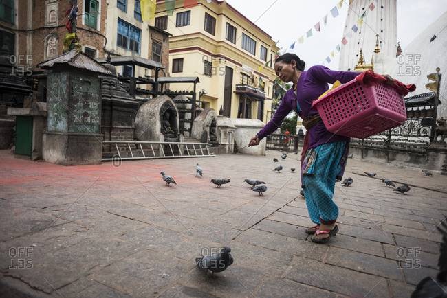 Kathmandu, Nepal - May 25, 2014: A woman shoos pigeons away while walking through a square in a city in Nepal