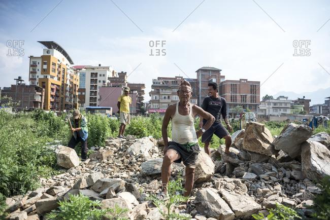 Kathmandu, Nepal - May 25, 2014: Men breaking rocks in a field at the slums of Thapathali, Kathmandu, Nepal