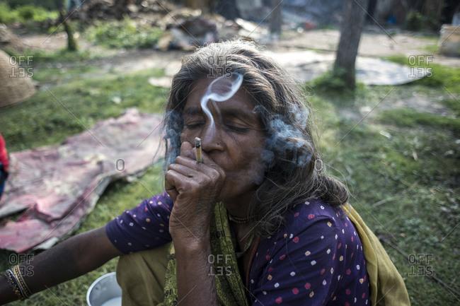 Kathmandu, Nepal - May 25, 2014: An old woman smokes a cigarette in the slums of Thapathali, Kathmandu, Nepal