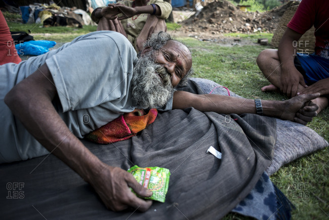 Kathmandu, Nepal - May 25, 2014: An old man lays on the grass in the slums of Thapathali, Kathmandu, Nepal