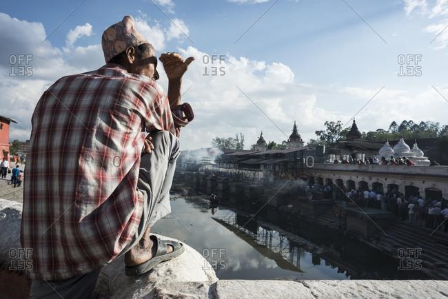 Kathmandu, Nepal - May 28, 2014: A man looks at a procession at Pashupatinath Temple in Kathmandu, Nepal